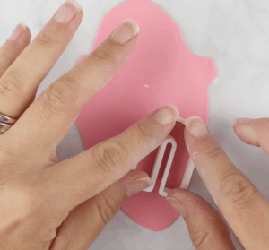 cutting polymer clay earrings with arched clay cutter using pink clay