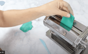 rolling teal clay through a silver pasta machine for polymer clay earrings